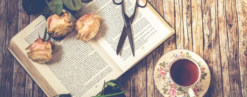 Buch aufgeschlagen mit Schere und Tee